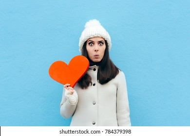 Funny Woman in Love Holding a Heart on Blue Background. Surprised Valentine Girl having a sudden crush