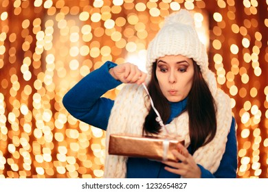 Funny Woman Opening Christmas Present Celebrating Winter Holidays. Impatient girl unwrapping Xmas present at outdoors party celebration
