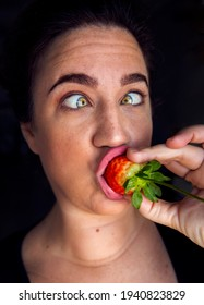 Funny woman portrait eating a strawberry