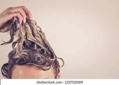 Funny woman pulls himself wet hair up. Close-up, space for text. Hair care concept.