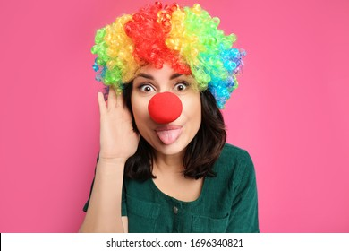 Funny woman with rainbow wig and clown nose on pink background. April fool's day