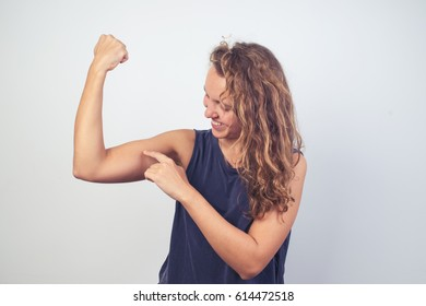 Funny woman showing muscles