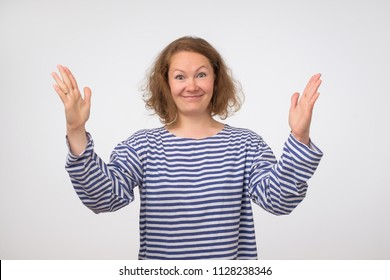 Funny woman in striped shirt showing something big in size with hands. emotions, facial expressions, feelings, body language, signs.