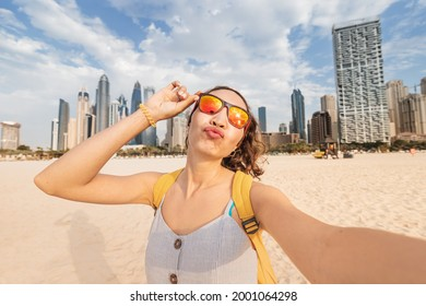 Funny woman takes a selfie photo against the backdrop of Dubai skyscrapers and parodies inflated lips and duckface