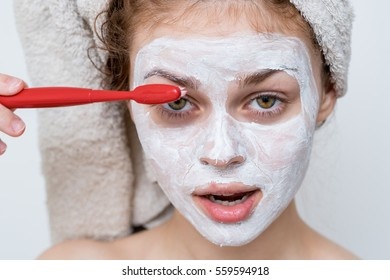 Funny woman with a toothbrush brushing eyebrows