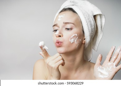 funny woman in a towel on the head happy cleanses the skin with