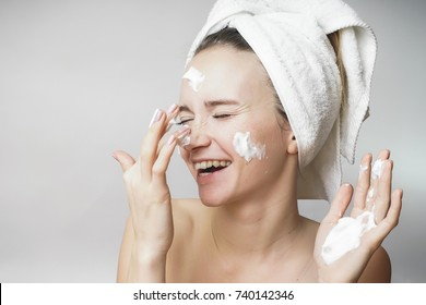 funny woman in a towel on the head happy cleanses the skin with foam on a white background isolated. Skincare cleansing concept