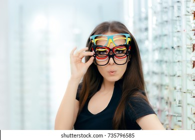 Funny Woman Trying Many Eyeglasses Frames in Optical Store Happy girl wearing lots of colorful spectacles at the same time
