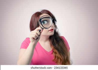 Funny woman using magnifying glass. Big zoom concept
