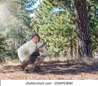 Funny woman wearing a dress, fur coat and boots holding a shotgun in the forest
