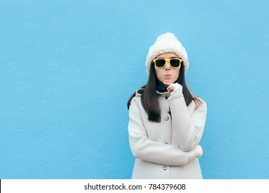 Funny Woman with Yellow Sunglasses Thinking on Blue Background. Cool girl wearing white beanie and coat having an idea