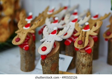 Funny wooden moose deers with red noses and Santa hats on traditional winter Christmas market in Munich, Germany