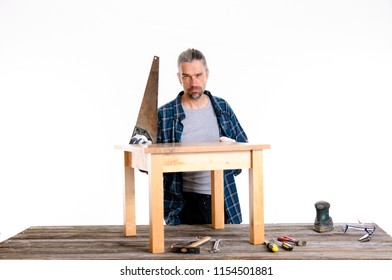 funny worker in blue plaid  shirt repair a table