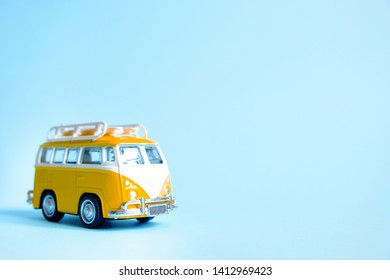 Funny yellow retro car with surfboard on blue background. Summer travel vacation concept. Summer holidays, road trip, vacation. Hippie minivan car on beach