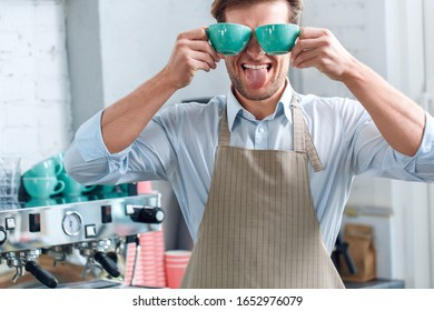 Funny young adult barista in uniform working in coffeeshop, standing near professional coffee machine, holding cups with beverage in hands, making fooling grimace and tongue out