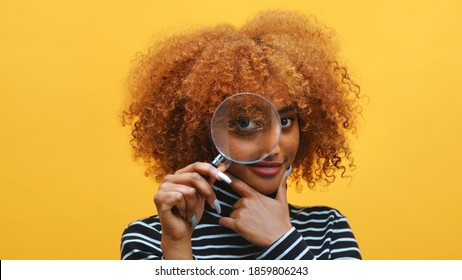 Funny young african american black woman with magnifier in hand shows eye through magnifying glass. High quality photo