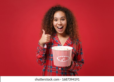 Funny young african american girl in pajamas homewear posing resting at home isolated on red background. Relax good mood lifestyle concept. Mock up copy space. Hold bucket of popcorn showing thumb up