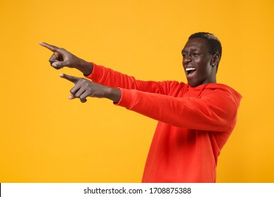 Funny young african american man guy in red streetwear hoodie posing isolated on yellow wall background studio portrait. People lifestyle concept. Mock up copy space. Pointing index fingers aside