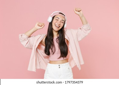 Funny young asian woman in casual clothes cap posing isolated on pastel pink background studio portrait. People lifestyle concept. Mock up copy space. Listening music with headphones, dancing