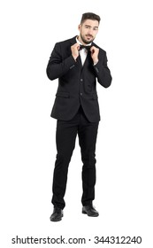 Funny young bearded man adjusting bow tie looking at camera. Full body length portrait isolated over white studio background.