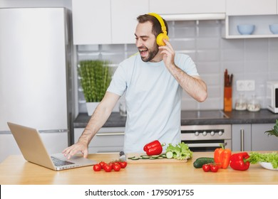 Funny young bearded man in casual t-shirt with headphones using laptop computer looking at recipe preparing vegetable salad cooking food in light kitchen at home. Dieting healthy lifestyle concept