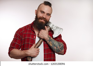 funny young bearded man hugging axe and looking at camera