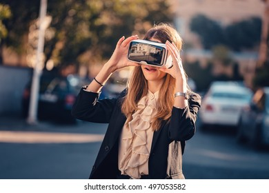 Funny young beautiful girl adjust on the head her virtual reality 3D video glasses VR headset dressed in a office outfit impressed by augmented reality on the street and beautiful autumn sun light