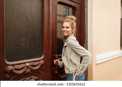 Funny young beautiful model woman with a smile in a vintage stylish jacket near an old wooden door