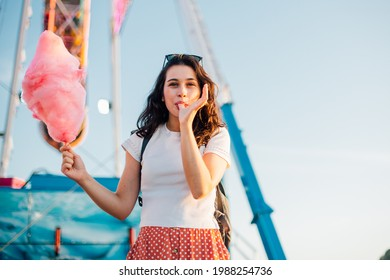 Funny young beautiful woman eating cotton candy and sucking her thumb at fairground