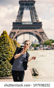 Funny young blonde woman portrait pointing the Eiffel Tower in Paris, France.