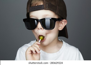 Funny Young Boy Eating A Lollipop.Fashionable child in sunglasses