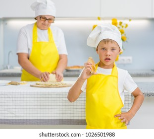 Funny young boy with a rolling pin in the kitchen, grandmom on the background