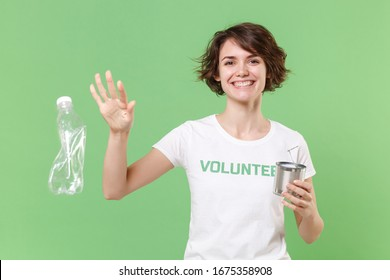 Funny young brunette girl in volunteer t-shirt isolated on pastel green background. Voluntary free work assistance help charity grace teamwork concept. Throwing trash empty plastic bottle hold tincan