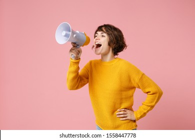 Funny young brunette woman girl in yellow sweater posing isolated on pastel pink wall background studio portrait. People sincere emotions lifestyle concept. Mock up copy space. Screaming in megaphone