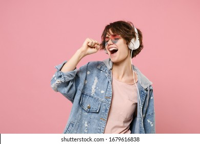 Funny young brunette woman girl in casual denim jacket, eyeglasses posing isolated on pastel pink background. People lifestyle concept. Mock up copy space. Listen music with headphones, sing song