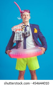 Funny young businessman in suit with beach accessories