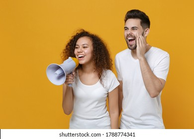 Funny young couple friends european guy african american girl in white t-shirts posing isolated on yellow background. People lifestyle concept. Mock up copy space. Scream in megaphone, looking aside