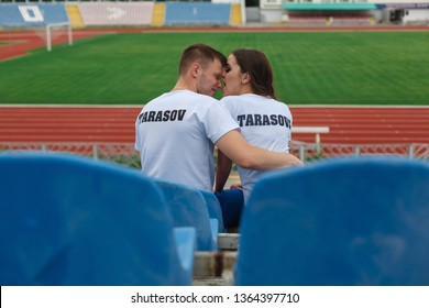 funny young couple hugging at a sports stadium. Couple  on empty tribune after football match. Active couple of soccer supporters. guy and girl kisses on the  stadium.