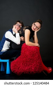 A funny young couple .Nerd,holding  red hairy heart.