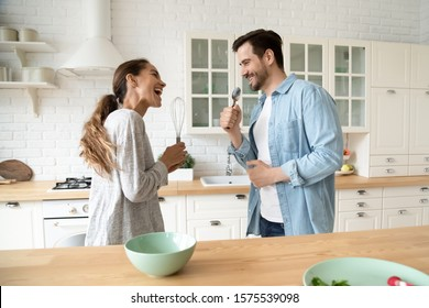 Funny young couple singing in kitchenware microphones in kitchen, happy carefree husband and wife hold beater spoon together having fun preparing dinner breakfast cooking dancing listen music at home