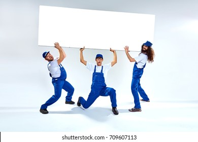 Funny, young craftsmen lifiting a heavy commercial board