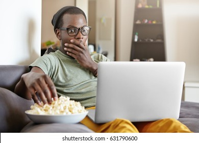 Funny young dark-skinned man sitting on grey sofa in living room with notebook pc on his lap, staring at screen with shocked or scared look, covering mouth with hand while watching scary movie