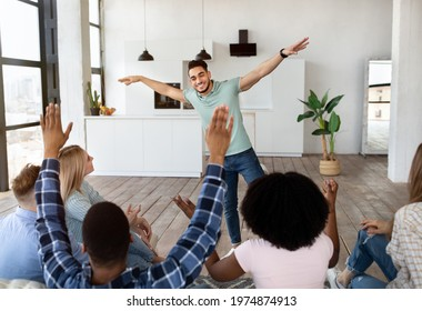 Funny young diverse friends playing guess who game, laughing, having fun together at home. Group of multiracial youth showing pantomime riddles or charades on student party indoors