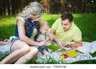 funny young family resting in city park, lovely couple reading book with his little son, concept happy family