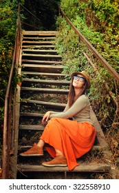 Funny young fashion girl making duck face against the old wooden stairs, outdoor.