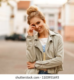 Funny young fashion model woman with a smile in a stylish jacket in a city