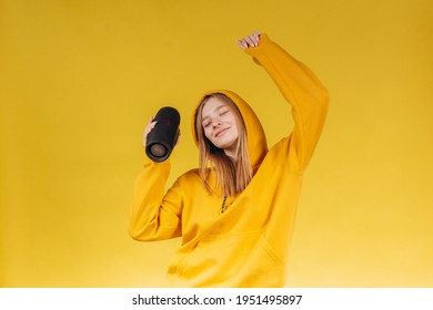 Funny young girl looking, waving hand, holding portable wireless bluetooth music speaker, isolated on yellow background. Girl in a yellow hoodie