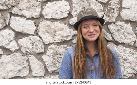 Funny young girl near a stone wall.