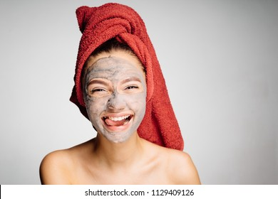 funny young girl with a red towel on her head showing a tongue, on her face a cleansing mask