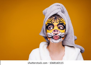 funny young girl with a towel on her head after a shower, face mask with an animal's muzzle, facial
